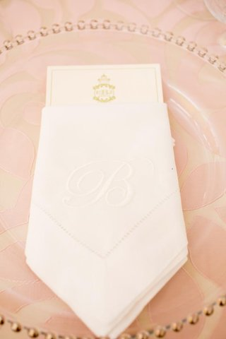 clear-charger-plate-with-white-napkin-embroidered-with-initial