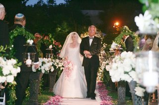 bride-wearing-an-a-line-gown-and-veil-is-escorted-by-her-father-down-the-aisle