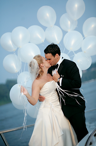 bride-and-groom-kiss-while-holding-balloons