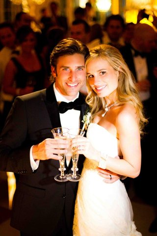 tuxedo-groom-and-strapless-bride-dress-with-champagne-flutes