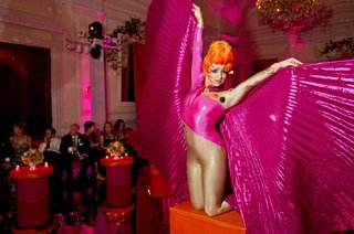 woman-in-body-suit-on-orange-pedestal