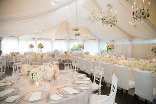 white-drapery-and-chandeliers-on-ceiling-of-tented-reception