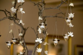 white-flowers-and-candles-hanging-from-tree-branches