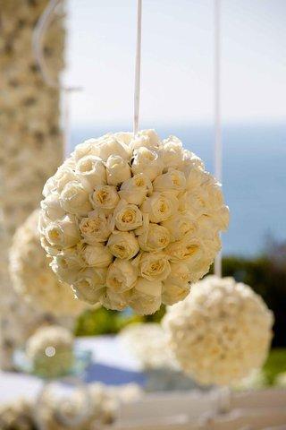 white-ribbon-suspending-rose-pomander-balls-at-wedding-ceremony