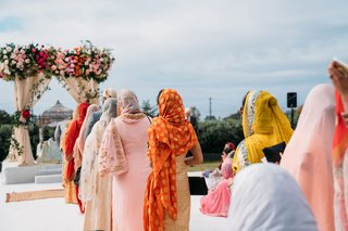 wedding ceremony guests and family walking to find their seats traditional ensembles pink orange