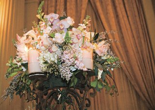 pink-and-white-flowers-in-the-center-of-a-candelabra-with-pink-candles