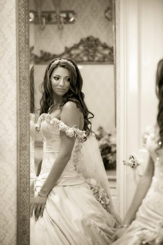sepia-tone-picture-of-bride-looking-in-mirror