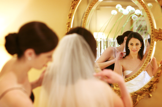 bride-gets-ready-in-front-of-a-gold-rimmed-mirror