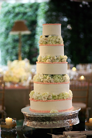 white-cake-with-pink-trim-and-green-flowers-between-each-tier