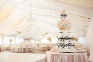pink-tablecloth-over-round-table-with-black-and-white-cake