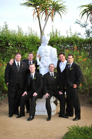men-in-tuxedos-next-to-white-statue-of-woman