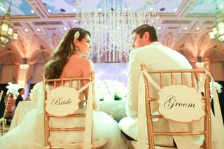 newlyweds-sit-in-chairs-with-bride-and-groom-signs-on-the-back