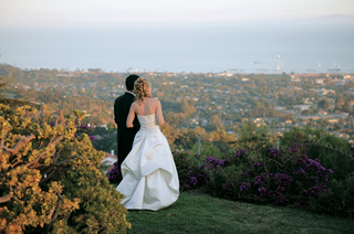groom-and-bride-in-ball-gown-look-out-at-ocean