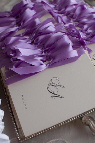 ceremony-program-with-monogram-tied-with-purple-bow