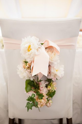 white-and-pink-flowers-hanging-from-pink-ribbon-on-chair