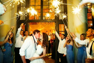 couple-leaves-reception-under-archway-of-sparklers-held-by-guests