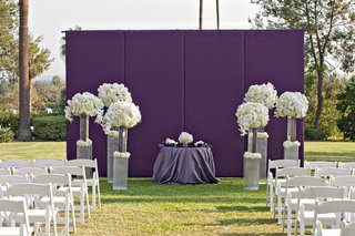 white-chairs-and-violet-wall-with-floral-arrangements