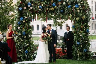 A Charming Fete Outdoor Ceremony Kiss greenery arch blue and burgundy flowers