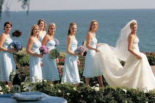 bridesmaids-holding-brides-train-with-ocean-background