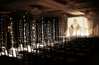wedding-ceremony-with-candles-and-orchid-strands-lining-an-aisle-to-a-chuppah