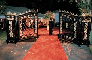 wedding-reception-with-a-black-and-gold-iron-gate-and-red-carpet