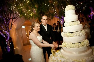 bride-and-groom-cut-into-towering-wedding-cake