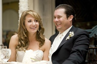 bride-and-groom-laugh-and-smile-during-wedding-reception