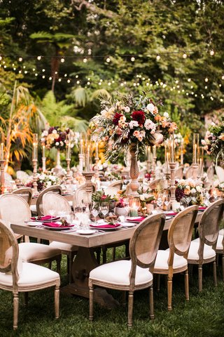 wedding-reception-outdoor-rustic-elegant-fall-color-palette-red-greenery-bistro-lights-cane-chairs