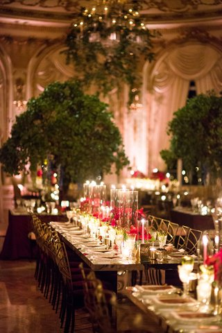 wedding-reception-tall-tree-centerpieces-long-mirror-table-taper-candle-candlelight-gold-chairs