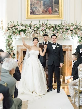 wedding-ceremony-oheka-castle-fireplace-at-altar-with-fresh-flower-garland-pink-white-greenery
