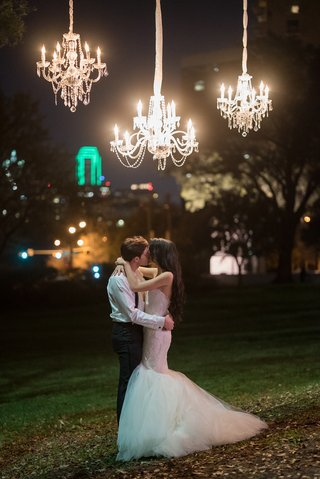 bride-in-nardos-deisgns-lace-mermaid-gown-kisses-groom-under-outdoor-chandeliers