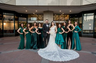 bride and groom with bridesmaids in emerald green dresses for reception mismatch gowns