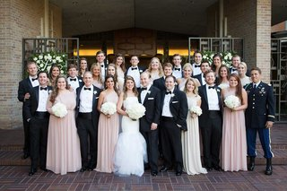 bride-and-groom-with-bridesmaids-in-pink-dresses-and-groomsmen-in-black-and-white-tuxedos-bow-ties