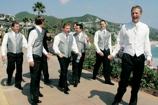 groom-and-groomsmen-walk-along-beach-without-suit-jackets