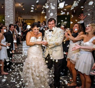guests-toss-white-rose-petals-at-bride-and-groom