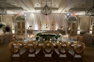wedding-reception-tufted-bar-gold-shelves-mirror-table-gold-chairs-low-centerpiece