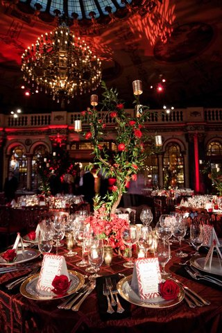 red-tablecloth-with-tree-centerpiece-and-red-flowers