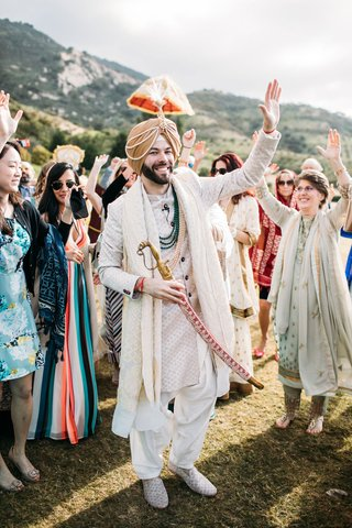 groom in traditional ensemble holding saber sword at sikh ceremony ranch wedding california