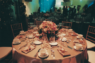 golden-table-with-pink-centerpiece-in-front-of-aquarium