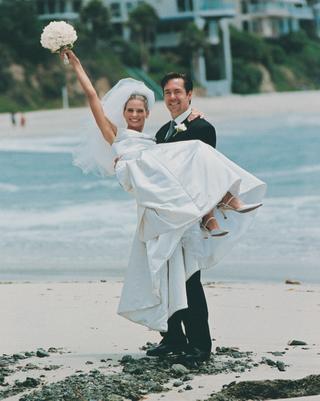 groom-holds-bride-on-laguna-beach-sand
