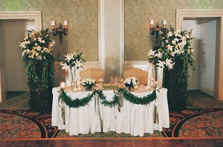 hotel-ballroom-sweetheart-table-with-green-garlands