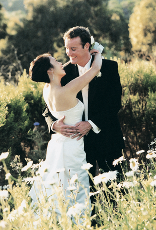 bride-and-groom-hug-in-white-daisy-field