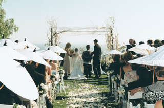 bride-and-groom-at-ceremony-altar-and-guests-on-grass