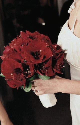 bride-holding-crimson-lilies-wrapped-in-white