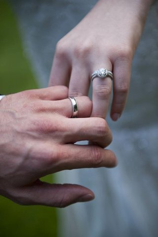 hands-of-bride-and-groom-with-respective-wedding-rings