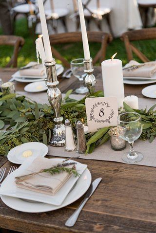 rustic-wedding-reception-wood-table-with-table-number-in-drawn-wreath-design-silver-candlesticks