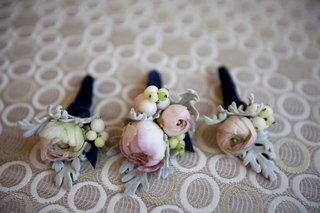 floral-boutonnieres-wrapped-in-dark-blue-ribbon