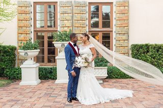 groom-in-blue-tuxedo-with-burgundy-lapels-bride-in-lace-cap-sleeve-wedding-dress-and-cathedral-veil