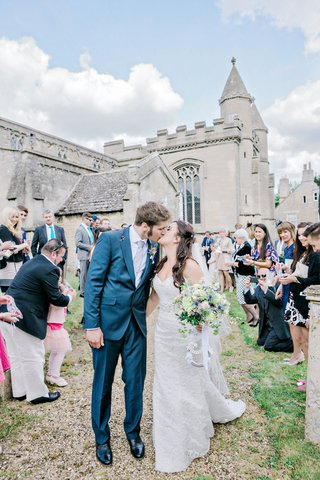 couple-kiss-coming-st-andrews-church-england-british-wedding-english-blue-tuxedo-suit-ceremony-exit