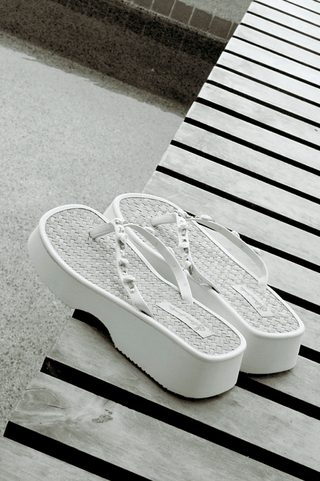 white-platform-flip-flops-with-rosettes-on-straps